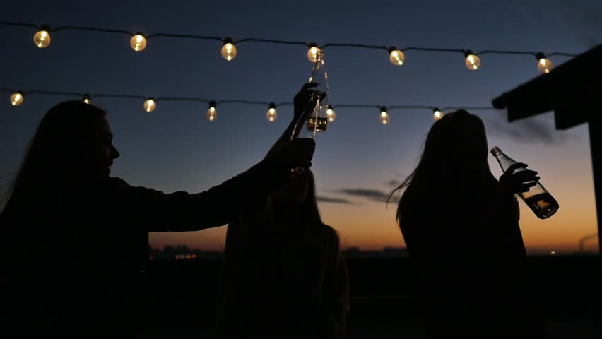 Silhouettes of young people toasting with bottles and dancing with raised arms to the music played by dj at rooftop party during beautiful city sunset   Shutterstock HD Video #1017958993