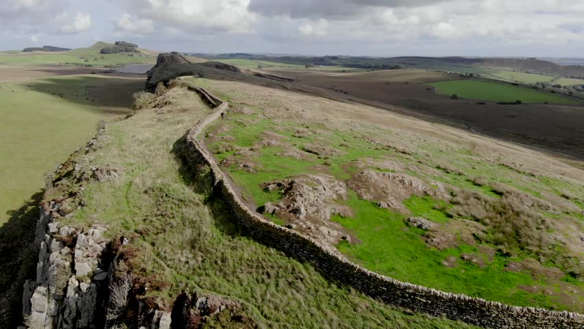 Aerial-Flying over ancient Roman wall (Hadrian's Wall) along the Scottish border-Unidentifiable hiker walks along the wall with a dog | Shutterstock HD Video #1017969313