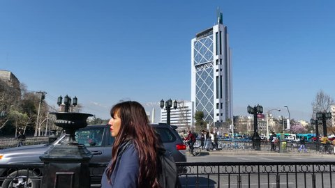 SANTIAGO, CHILE - Sep 11 2018. Lively view from the Pio Nono bridge: Andes Mountains and Telephone Tower on the back, with the Plaza Italia Obelisk, Mapocho River, pedestrians and cars all visible.