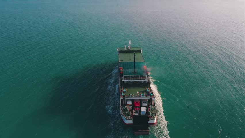 Above the ferry going on the sea. The ferry boat carries passengers and transport along the green sea | Shutterstock HD Video #1017998443