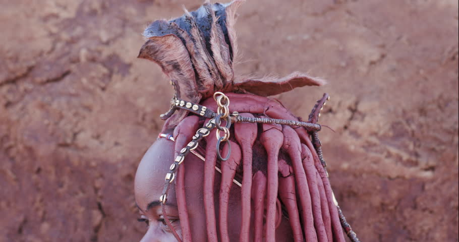 4K close-up tilt down view of a pretty Himba girl showing head gear and neck jewellery,Namibia