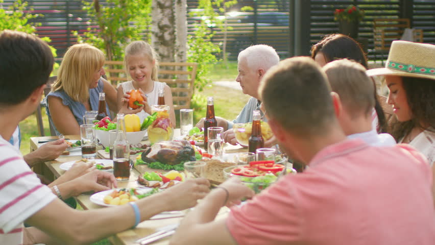 Big Family Garden Party Celebration, Gathered Together at the Table Relatives and Friends, Young and Elderly are Eating, Drinking, Passing Dishes, Joking and Having Fun. | Shutterstock HD Video #1018049473