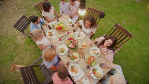 Big Family Garden Party Celebration, Gathered Together at the Table Relatives and Friends, Young and Elderly are Eating, Drinking, Passing Dishes, Joking and Having Fun. Top Down Camera Shot.