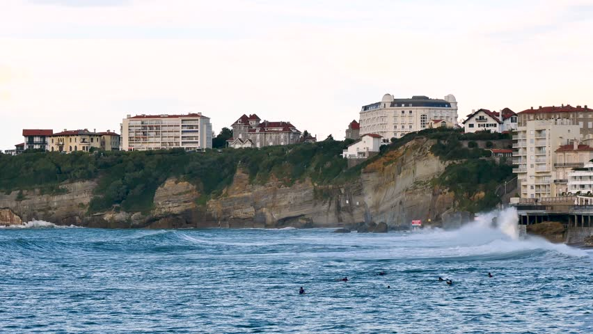 Coast of the city of Biarritz, next to the large beach. Filmed in October 2018. There are big waves hitting the cliff. Buildings above the cliff.