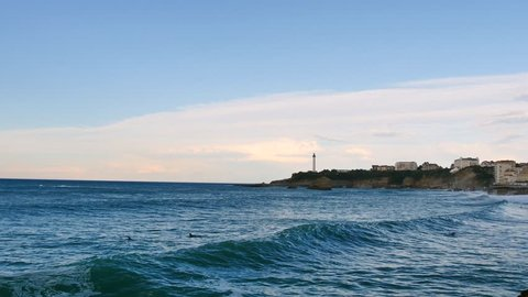 Landscape of Biarritz, a city in southwestern France. View of the city lighthouse and surfers in the water. Filmed in October.