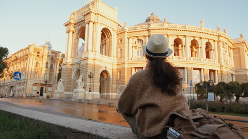 Woman traveler with backpack holding dog examines architectural monument .  Odessa Opera Theatre. | Shutterstock HD Video #1018179343