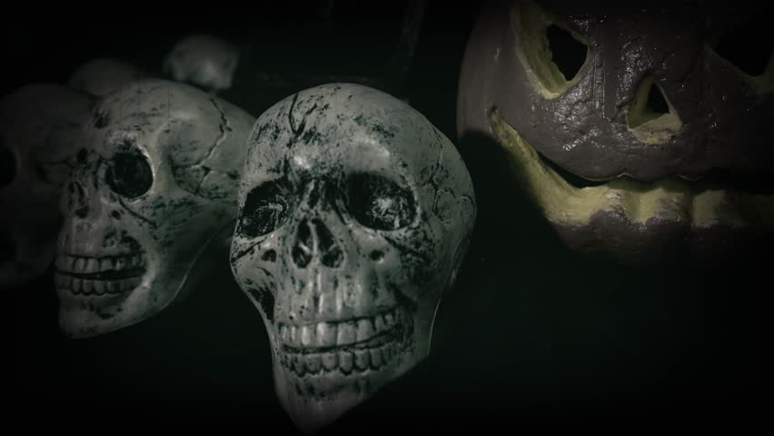 Old film look of halloween set decoration with skulls, grave and jack o'lantern   Shutterstock HD Video #1018184713
