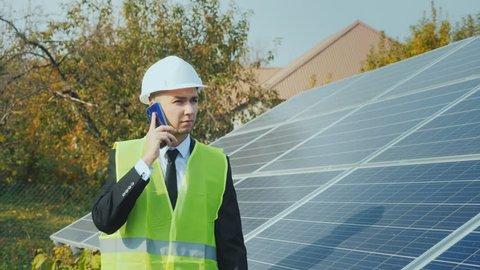 A worker in a helmet walks along a row of solar panels, speaks on the phone. Steadicam shot