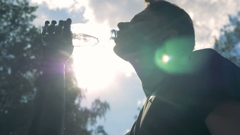 Close up of a young man drinking water with his artificial hand