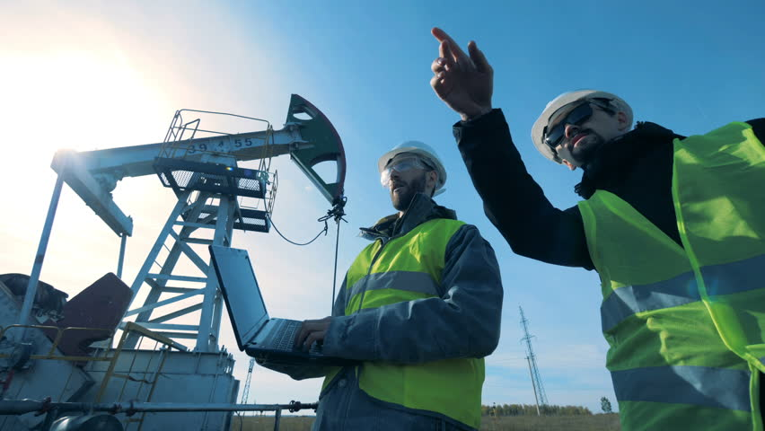 Men with a laptop walk near working oil derrick. Fossil Fuel, Oil industry concept.