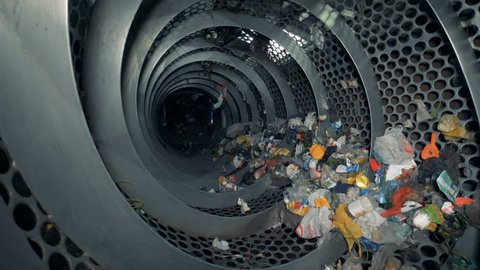 Lots of trash in a recycling center. Recyclable garbage rotates in a special machine at a plant.