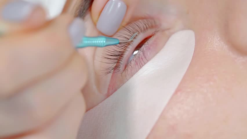 master of laminating of eyelashes is fixing hair on eyelid of young female client, laying it on silicon roll #1018189753