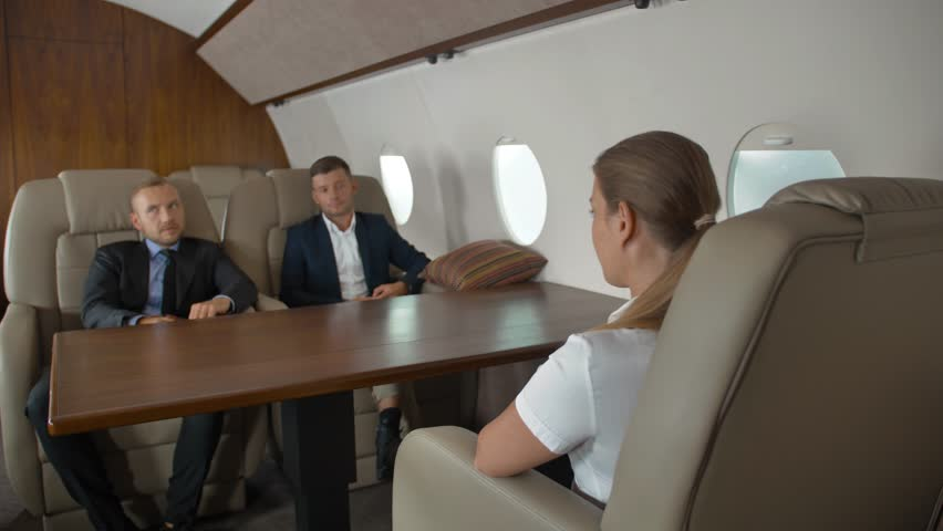 Premium view of businesspeople have meeting in corporate jet. Two confident male entrepreneurs and successful female businesswoman. first class, camera focus on woman. | Shutterstock HD Video #1018189813