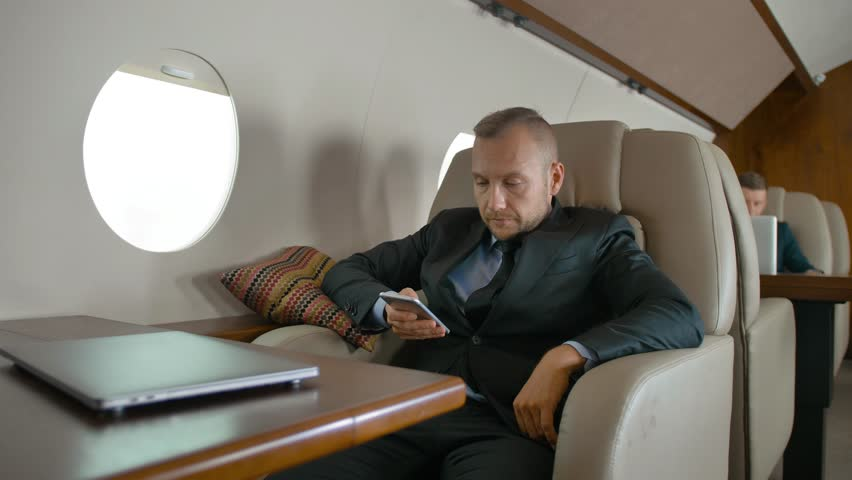 Confident entrepreneur traveling on his private jet and chatting on cell phone. He write sms while flight hi first class plane. | Shutterstock HD Video #1018189843