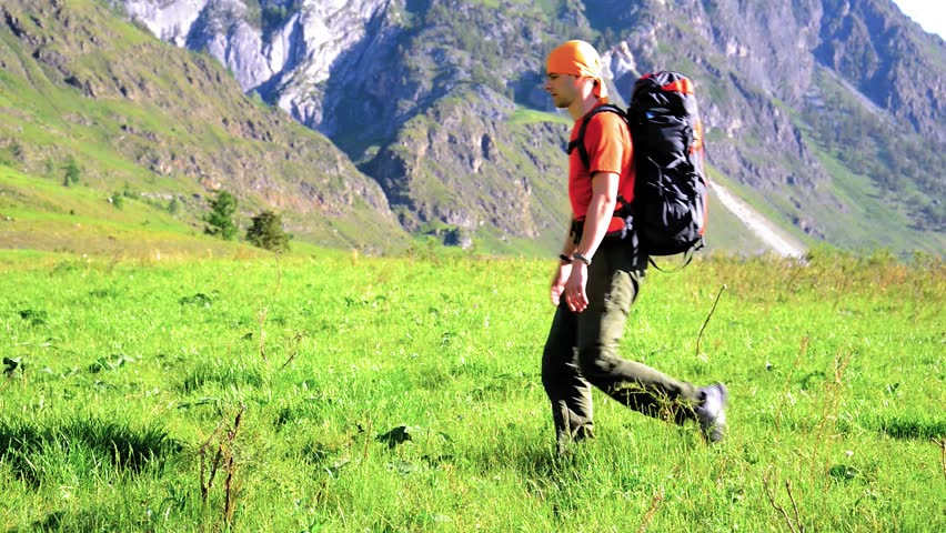 FHD Hiking man walking on green mountain meadow with backpack. Tourist travelling in sunny outdoors. Summer sport and recreation concept. | Shutterstock HD Video #1018195303