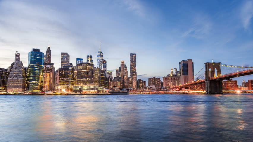 4k cinemagraph of New York City Manhattan, financial district night skyline, cityscape at Brooklyn bridge park during sunset, dusk, twilight,  skyscrapers, moving traffic, cars, light streaks