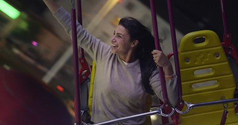Portrait of a beautiful young woman (girl) having fun on the rides at the Luna Park. Concept: Happiness, freedom, fun.
