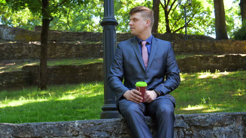 A young handsome guy (man) sits in a suit in a park, drinks from a plastic cup, watches time. Concept: Coffee, Tea, Time, Watch on hand, Glass, Park, Lifestyle.