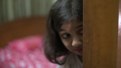 A lonely little girl scared and hiding behind a door in her room. Scared of pedophile, torture and domestic violence of parents and shocked of something