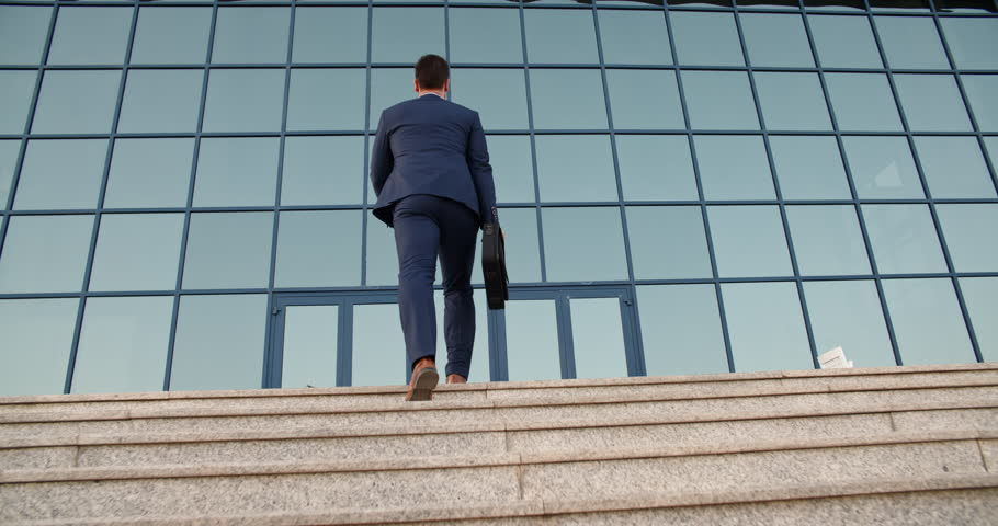 Confident multiethnic businessman in suit and tie going up the stairs of a business centre being late for work - 4k