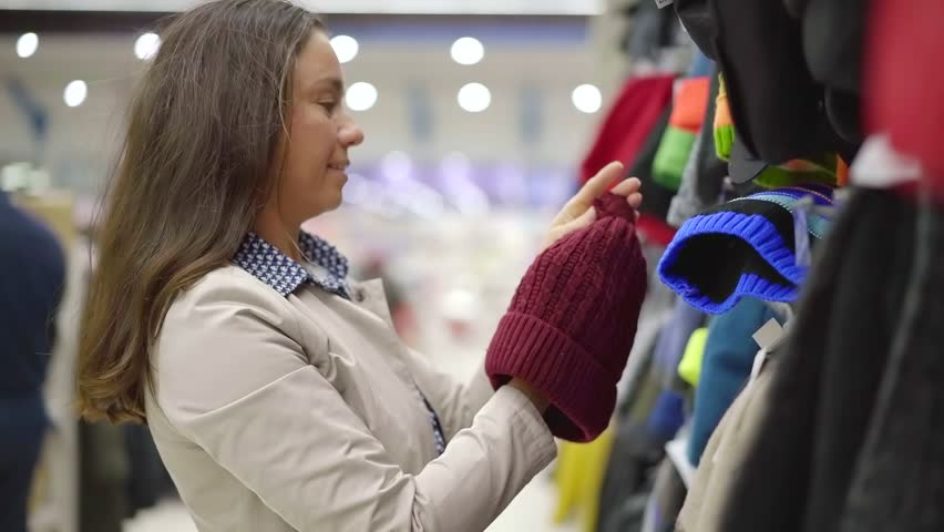 adult woman is choosing winter hats for her children in clothing store, taking different from rack