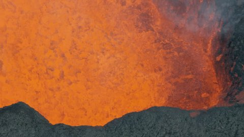 Aerial view of red hot magma in motion erupting from the earths crust with lava rock cooling toxic gases a natural phenomenon RED WEAPON