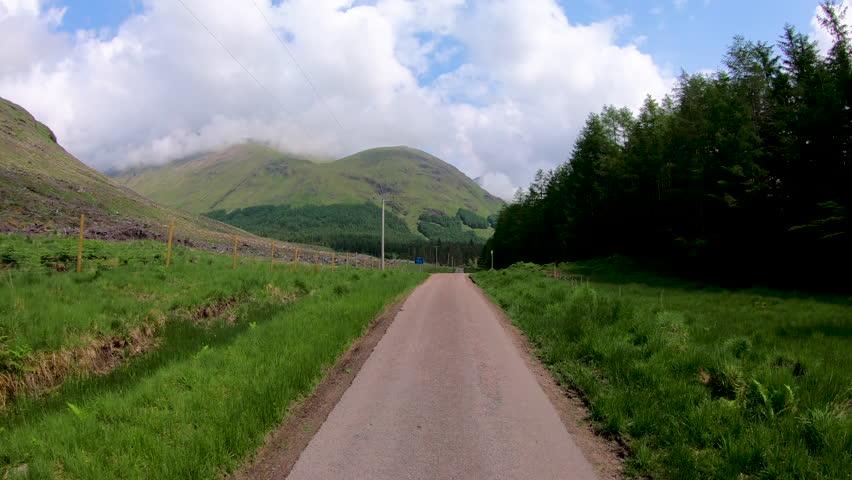 POV scenic driving in Glen Etive Scottish highland landscape mountain slopes rural evergreen forest valley wilderness Scotland UK Europe  | Shutterstock HD Video #1018450603
