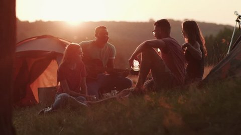 Young real friends camping together and drinking beer, cocktails by tents in bright sunset light. Concept about camping, nature and vacations. Tourism, active lifestyle, having fun