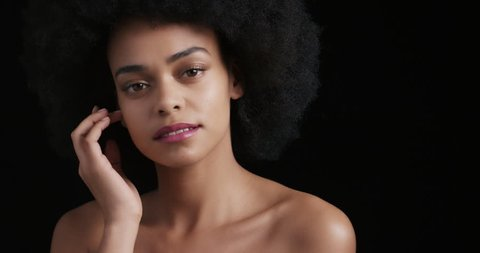 portrait attractive african american woman touching face with hands caressing smooth healthy skin complexion enjoying perfect natural beauty funky afro on black background