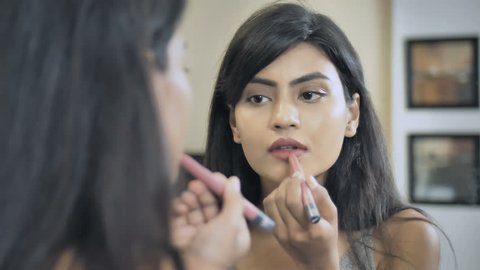 A close up shot of a beautiful girl applying lipstick on lips looking in the mirror