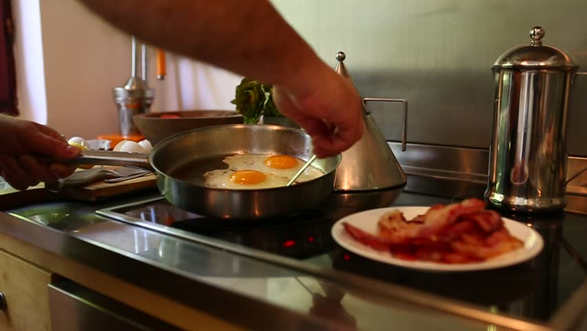Footage of man cooking sunny side up eggs, making eggs and bacon breakfast. Close-up video. Modern home kitchen, daylight. No face, hands only. | Shutterstock HD Video #1018541263