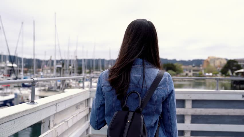 Asian backpacker walking close the handrail seeing the view. The Fisherman's Wharf in Monterey California is a popular tourist destination along the central Pacific Coast with boating excursions. | Shutterstock HD Video #1018585603