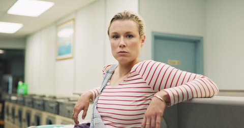 Portrait of young confident woman sitting on a counter near washing machines interior small laundromat with bright interior lighting. Wide to Close up shot on 4k RED camera on a gimbal.