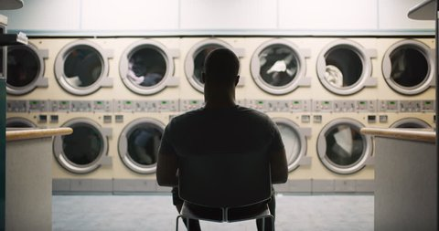 Young man sitting in a chair with earbuds and watching the laundry machines running in interior small laundromat with bright interior lighting at night. Wide to Medium shot on 4k RED camera on gimbal.