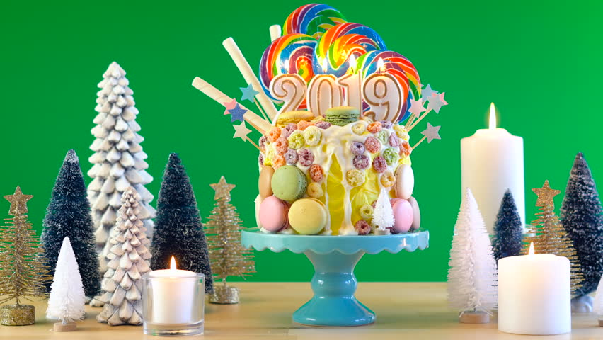 happy new years candy land lollipop drip cake with 2019 candles on greenscreen background