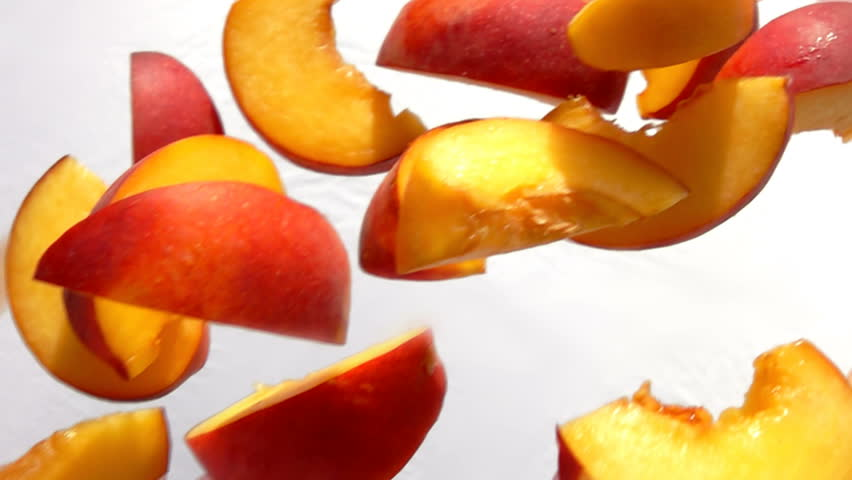 Slices of peach fly close-up on white background in slow motion | Shutterstock HD Video #1018664563