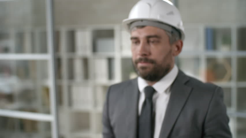 Medium shot of bearded man wearing suit and hard hat holding futuristic mobile phone. Footage suitable for adding AR graphics | Shutterstock HD Video #1018679413