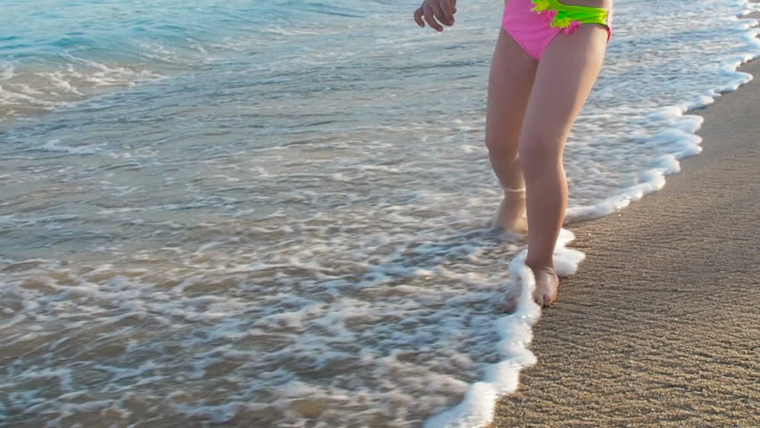 A child walks through the waves. Feet of a child on the beach. #1018680853