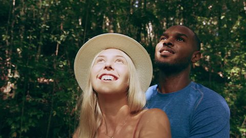 Happy interracial couple happily looking up and pointing in Australian rainforest through shaded green lush trees during daytime. Close up shot on 4k RED camera.