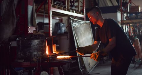 Male craftsman taking a piece of red hot metal and hammering the piece in interior blacksmith workshop in soft day lighting. Medium shot on 4k RED camera.