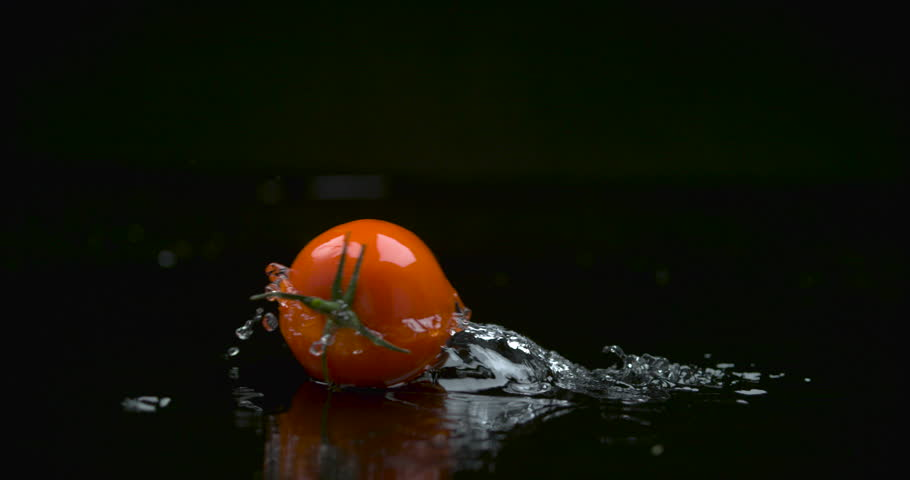 Red plump tomato rolling across water against a black background in soft studio lighting. Medium shot on 4k RED camera.