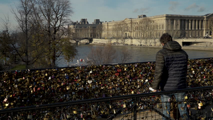 Paris, France - 01 09 2018: PARIS, FRANCE - JANUARY 9, 2018: Loving couple attacks the padlock at the famous Pont Neuf during a sunny day