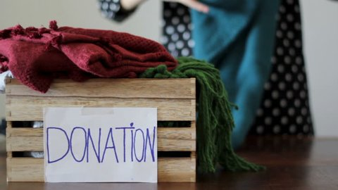 Woman folds clothes and puts inside a box for donation