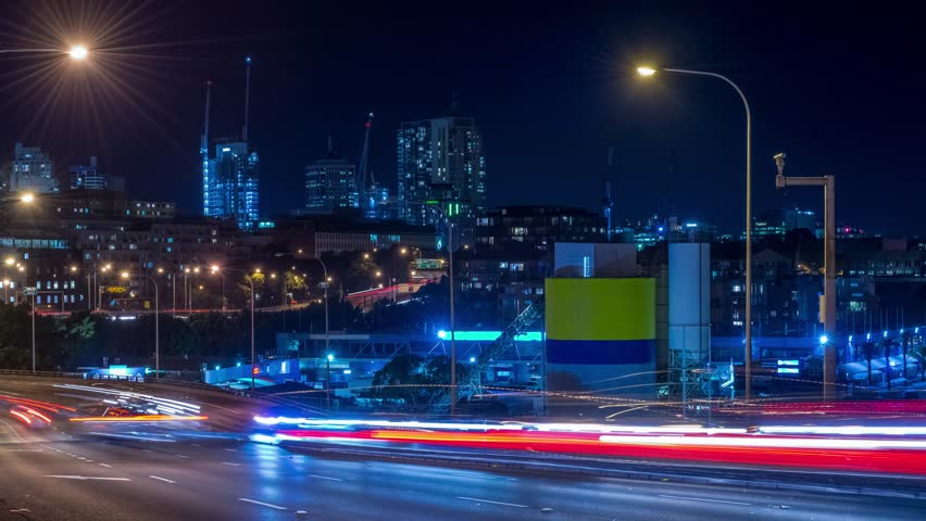 Long exposure time lapse footage with a slide effect of a busy road, opposite view from Anzac Bridge with the CBD of Sydney in a background | Shutterstock HD Video #1018772353