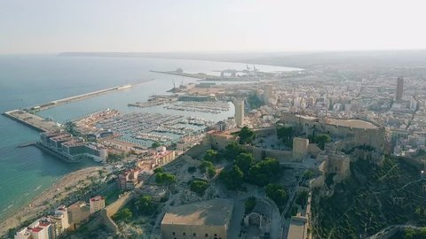 Aerial shot of Alicante cityscape and seaport behind Santa Barbara castle, Spain