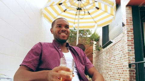 Young attractive man sitting at restaurant talking to friend having a beer on a patio with other patrons in the background. Medium close on 4k RED camera.
