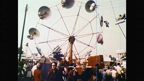 1970s: UNITED STATES: fairground wheel in action. People get on fairground ride. Child on fairground ride. North Carolina fairground attraction