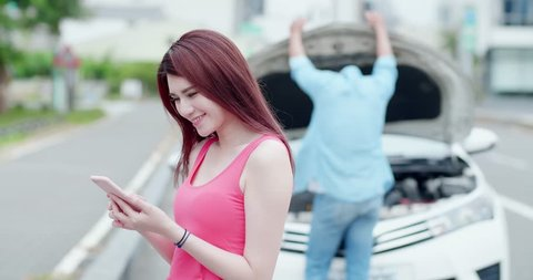 young woman using mobile phone and do not worry with broken down car on street