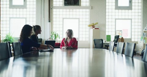 Female worker gets laid off at big board room table in hipster industrial office during the daytime. Wide to long shot on 4K RED on a gimbal dolly in.