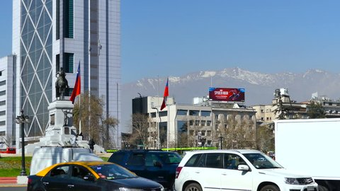 SANTIAGO, CHILE - Sep 11 2018. View of Plaza Baquedano and monument of a horse mounted general in front of the Telefonica skyscraper. Andes Mountains in the background, traffic on the bottom frame.